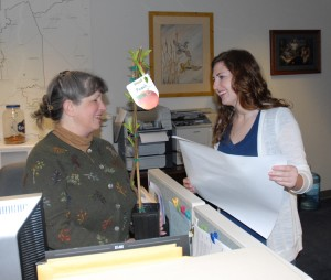 CDFA's Corinne Madison delivers a tree and an Ag Day sign to Rebecca Wood in Assemblyman Bill Berryhill's office.