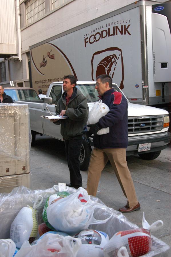 Jeff Cesca of CDFA (R) carries frozen turkeys destined for Foodlink