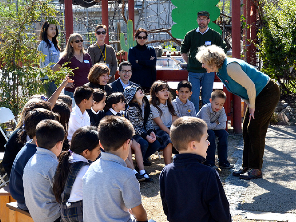 CDFA Secretary Karen Ross, seated center, joins second graders from St. Leo the Great School in San Jose for an edible garden tour.