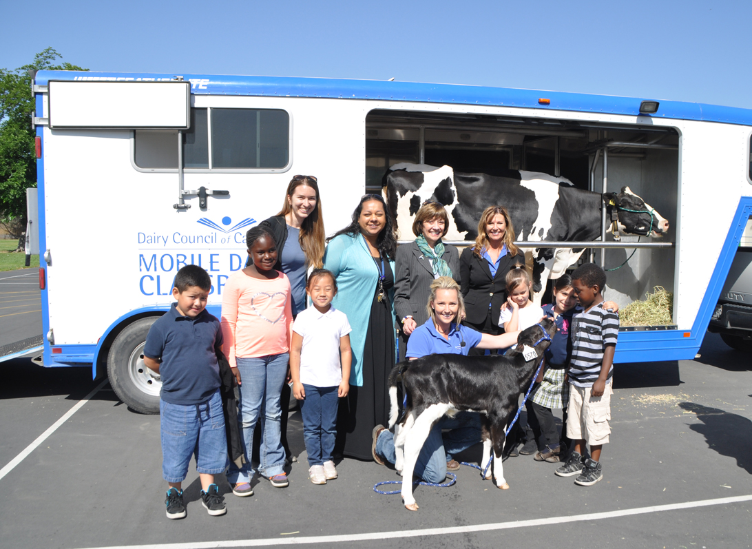 Secretary Ross (center) with students at Pacific Elementary School, principal Dr. Shana Henry (left), Sarah Hanson of CDFA's Farm to Fork Office (far left), Tammy- Anderson Wise, CEO of the Dairy Council of California (right), instructor Kimberlee Youman (kneeling) and Tootsie the calf.