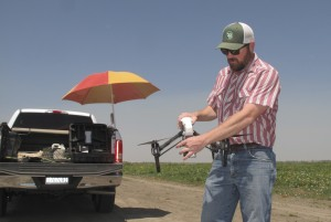 Danny Royer, vice president of technology at Bowles Farming Co., prepares to pilot a drone over a tomato field near Los Banos, Calif. The farm hired Royer this year to oversee drones equipped with a state-of-the-art thermal camera. The drone can scan from a bird's-eye view for cool, soggy patches where a gopher may have chewed through the buried drip irrigation line and caused a leak of water, a precious resource in drought-stricken California. On the farm's 2,400-acre tomato crop alone, this year drones could detect enough leaks to save water needed to sustain more than 550 families of four for a year. (Scott Smith/Associated Press)
