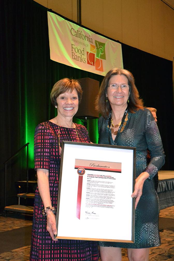 CDFA Secretary Karen Ross (left) presents a proclamation to California Association of Food Banks Executive Director Sue Sigler.