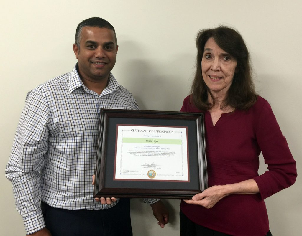 CDFA science adviser Dr. Amrith Gunasekara presents a proclamation from Secretary Karen Ross honoring the USDA's Luana Kiger for her service to CDFA's Environmental Farming Act Science Advisory Panel