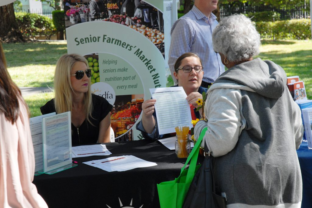 Crystal Myers (left) and Monica Pedigo with CDFA's Office of Grants Administration helped seniors find certified farmers' markets in their region that participate in the Senior Farmers' Market Nutrition Program.