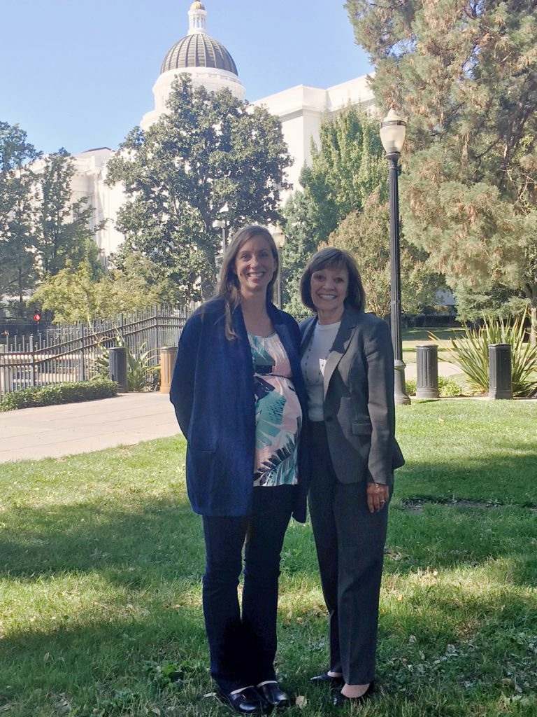 A photograph of CDFA Secretary Karen Ross with the department's new Farm Equity Advisor Thea Rittenhouse. The two are standing in Capitol Park with the dome in the background.