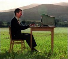 A man in a field sits at a computer workstation