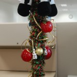 A coat rack decorated with Christmas tree ornaments