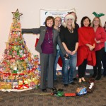 Secretary Ross and DMS employees pose near a tree made of canned goods encircled by a toy train