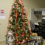 A Christmas tree with a lot of canned food under it