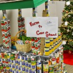 A fruit stand built out of canned goods, decorated with Christmas lights