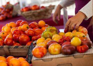 A customer choosing fresh vegetables at a market