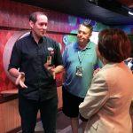 Luis Delgadillo walks through an exhibit with Rick Pickering and Karen Ross