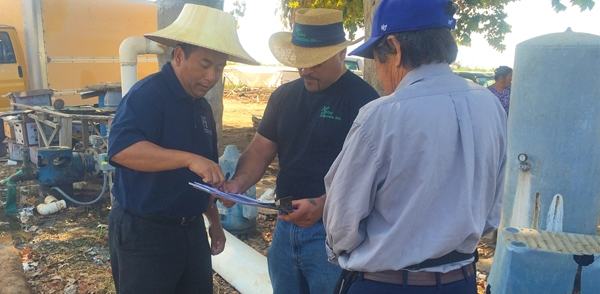 Michael Yang, UC Agriculture and Natural Resources, and Antonio Piña, AgriValley, meet with a Hmong farmer to plan a new irrigation system. Photo by Ruth Dahlquist-Willard.