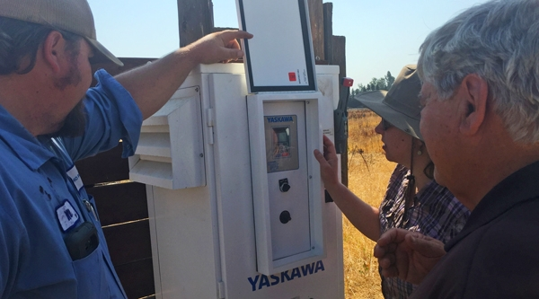 Ruth Dahlquist-Willard (center) with a variable frequency drive installed through the SWEEP program. VFDs can increase pump efficiency and lower energy costs