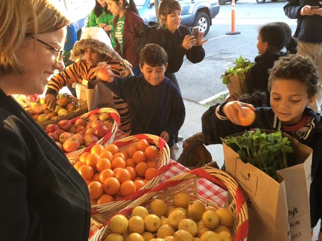 CDFA Deputy Secretary Jenny Lester Moffitt helps students choose fruits and vegetables.
