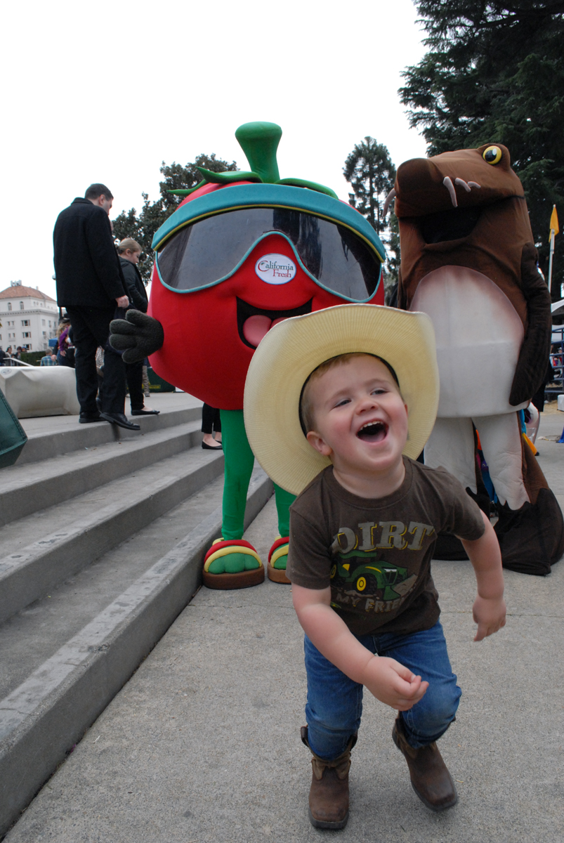 A child in a cowboy hat runs from costumed mascots at Ag Day