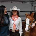 Assemblymember Sabrina Cervantes and Miss Rodeo California Amanda Hop posing with horses