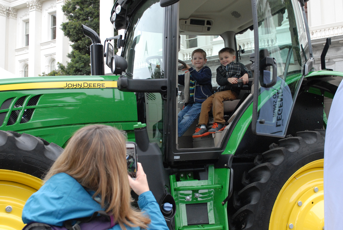 Two children sitting in a large tractor on Ag Day