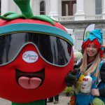 A girl poses with the California Fresh tomato mascot