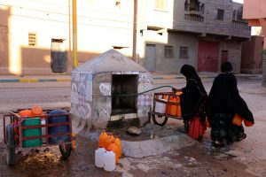 Moroccan women fill up containers with water from a hose
