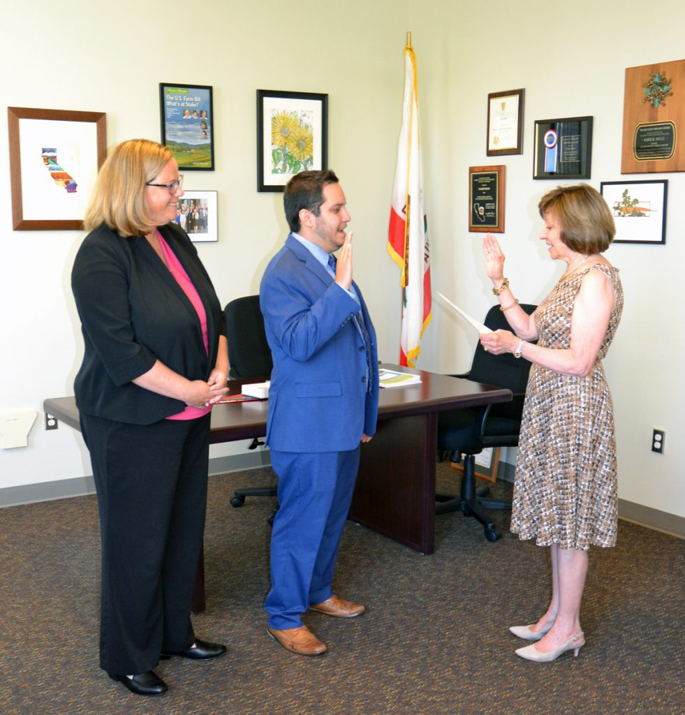 CDFA Secretary Karen Ross and newly appointed Deputy Secretary Arturo Barajas face each other with right hands raised as they read the oath of office. Undersecretary Jenny Lester Moffitt stands to the left as an official witness to the oath.