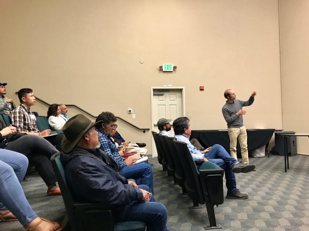 Photograph of Michael Wolff (CDFA) presenting in front of a theater-style room full of farmers and ranchers.